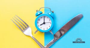 Blue and yellow background with a crossed knife and fork and a small blue clock to represent intermittent fasting