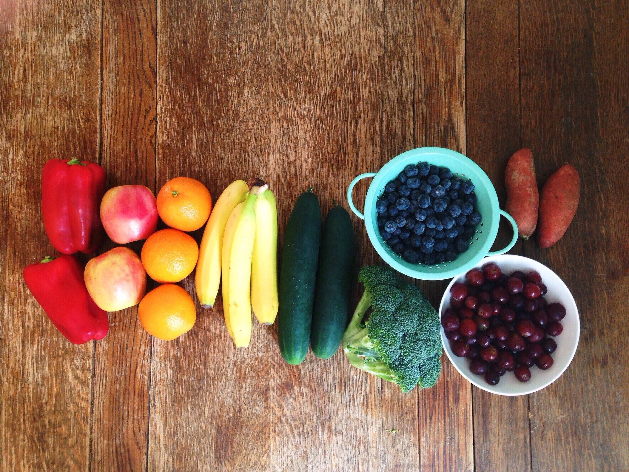 Rainbow of fruits and vegetables on a wooden table