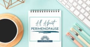 """Image of notepad that says """"All About Perimenopause"""" with a coffee cup, keyboard and pastel pens."""