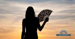 Silhouette of woman fanning herself watching a hot summer sunset.