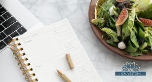 A small salad next to a notebook/planner and laptop on a desk with the Galveston Diet logo in the bottom right corner.