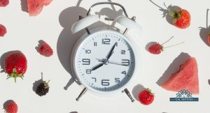 Intermittent fasting clock surrounded by fruit