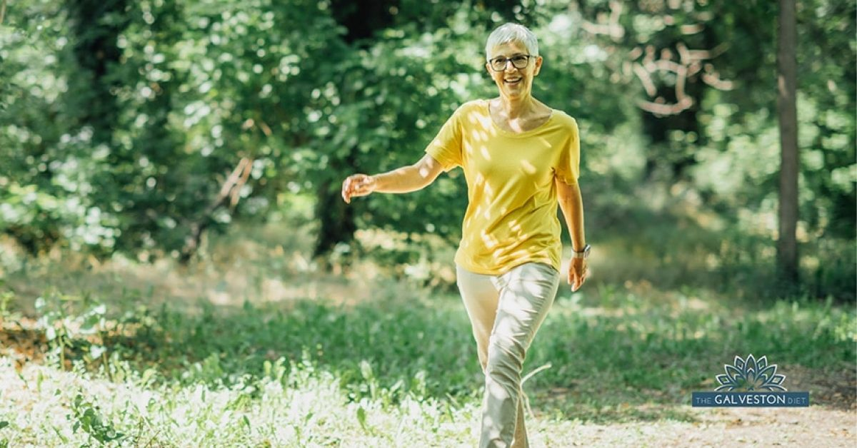 A middle aged woman in menopause smiles as she walks down a forested trail